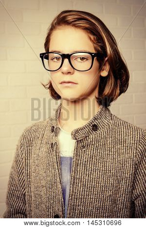 Portrait of a serious twelve year old boy wearing glasses. Boy teenager. Education.