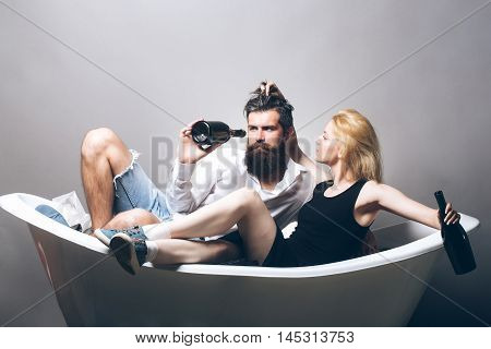 young drunk couple of blonde pretty girl and bearded man with long beard holding wine bottles laying in bathtub on grey background