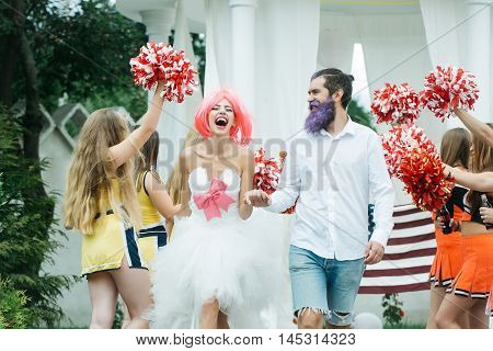 young glamour happy couple of pretty woman with orange hair and bearded handsome man with blue beard near cheerleaders holding pompoms
