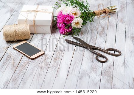 Handcrafted gift box and pink chrysanthemum flower on the wooden background. Concept of natural style design.