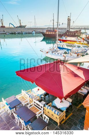 RETHYMNO GREECE - OCTOBER 16 2013: The taverns of the old harbor protect the outdoor terraces with the sunshades hiding the tables and chairs from the sun on October 16 in Rethymno.