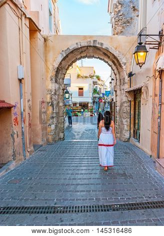 RETHYMNO GREECE - OCTOBER 16 2013: The Guora Gate leads to the old town with the maze of the narrow streets and various tourist stores and stalls on October 16 in Rethymno.