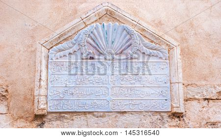 RETHYMNO GREECE - OCTOBER 16 2013: The old arabic inscription carved on the marble block is built in the house's wall on October 16 in Rethymno.
