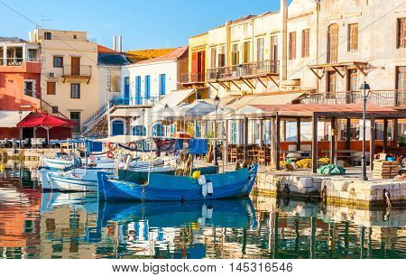 RETHYMNO GREECE - OCTOBER 16 2013: The walls of old houses are warmed by the morning sun and the fishing boats are dreaming in quiet old harbor on October 16 in Rethymno.