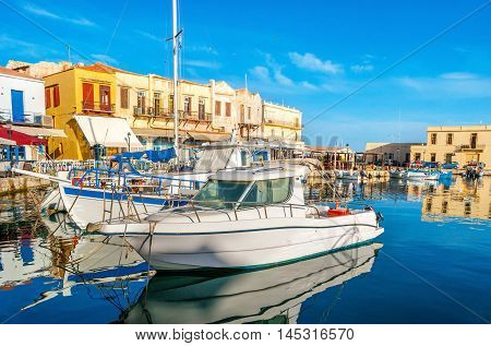 The beautiful tourist boats and yachts in the old harbor of Rethymno are the best choice to make a trip along the coast and discover the fishing villages and sites Crete Greece.