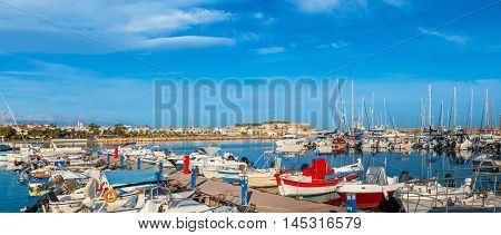 Panorama of the new port with the modern motor boats and yachts and the old town embankment on the background Rethymno Crete Greece.