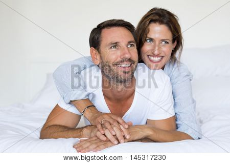 Mature lovely couple lying and having fun on bed. Close up portrait of romantic young couple in bed at home. Cute cheerful lovers enjoying on bed and looking up.