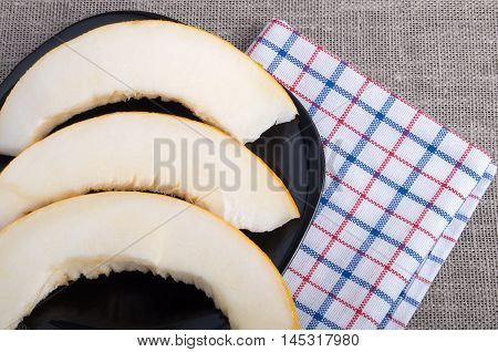 Melon Slices On A Black Plate On Fabric Background