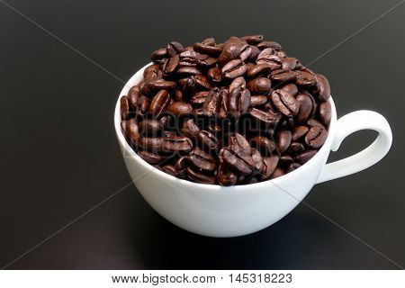 White small coffee cup filled with freshly roasted dark coffee beans isolated on dark brown background