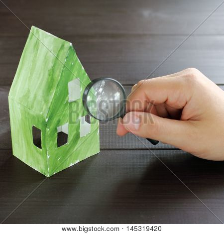 thorough inspection the concept of a magnifying glass green paper ecological home / check environmental performance