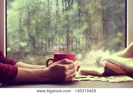 red mug of hot drink when behind a window is rain / cozy home atmosphere