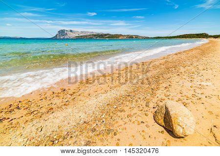 orange pebbles in Capo Coda Cavallo shore Sardinia