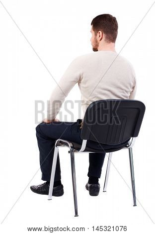 back view of business man sitting on chair. bearded man in a white warm sweater sits on a chair. Side view.