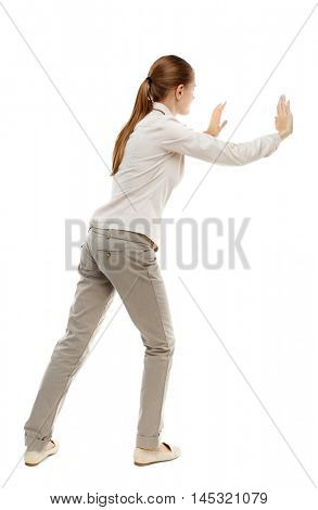 back view of woman pushes wall. Isolated over white background. Skinny girl in white denim suit shoves the load side.