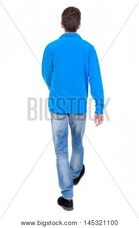 Back view of going handsome man. walking young guy . Curly boy in a warm blue sweater goes away.