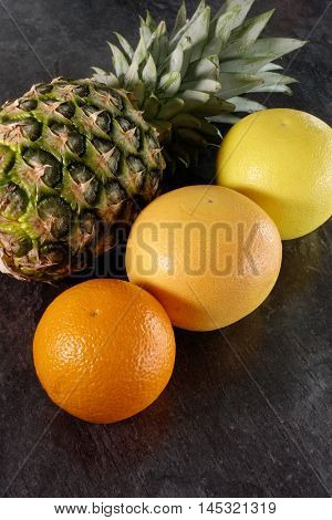 Composition of whole fresh fruits on black marbled worktop. One pineapple one orange and two grapefruits.