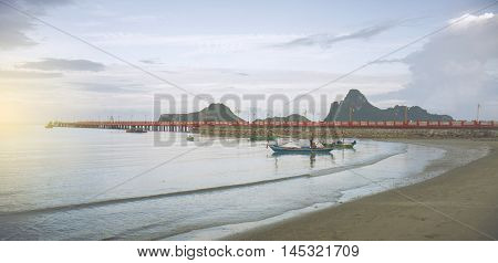 view of peace blue sea beach with red bridge and long big mountain sky background sunlight effect on the left side of picturefiltered image