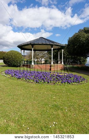 British public garden with Victorian pavilion and beautiful flowerbed full of primroses.