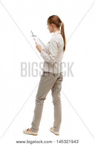 back view of stands woman takes notes in a notebook. Isolated over white background. Skinny girl in white denim suit instructs reading from a notebook.