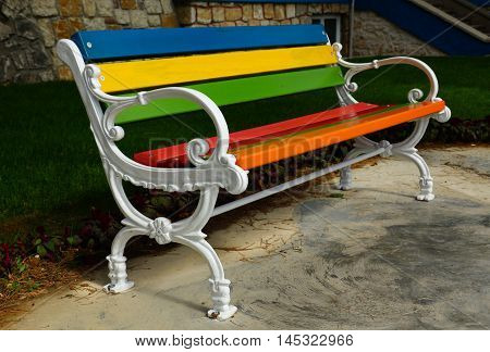 A colorful bench in the park. A lovely bench to sit.