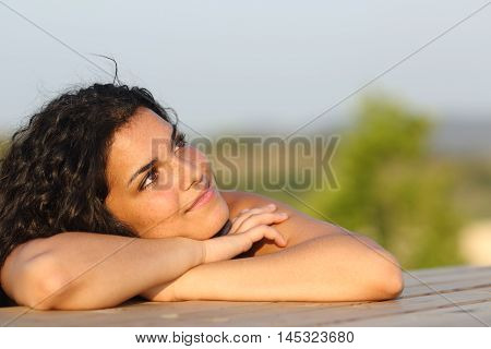 Candid girl dreaming and thinking leaning on a table outdoors