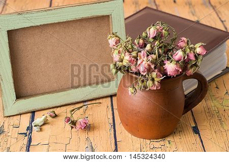 Earthenware mug with dry flowers, photo frame and photo album on the old wooden table.