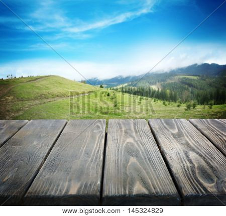Wooden board and summer forest on mountain slopes