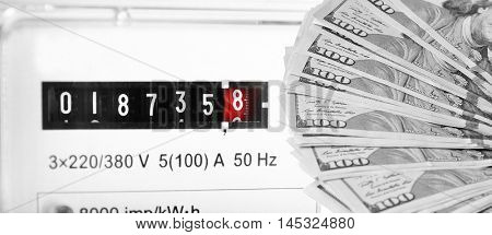 American dollars and electric meter display background.