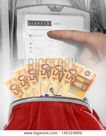 Red purse with euro banknotes and male finger pointing on electric meter display.