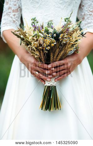 bride hand with bouquet of dried flowers and wheat ears in hands