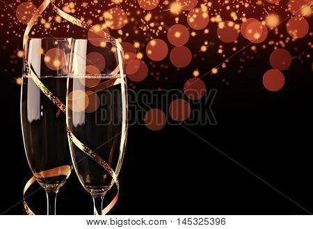 Two champagne glasses with streamer and bokeh lights on black background. Christmas celebration concept.