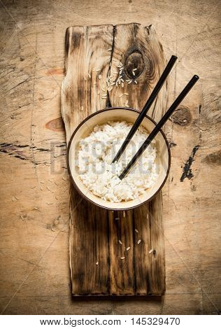 Boiled rice with chopsticks. On a wooden table.