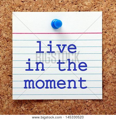 The words Live in the Moment printed on a note card pinned to a cork notice board as a reminder to be mindful and be in the present