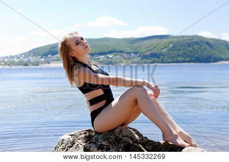 Blonde In Black Bathing Suit Sitting On Large Rock