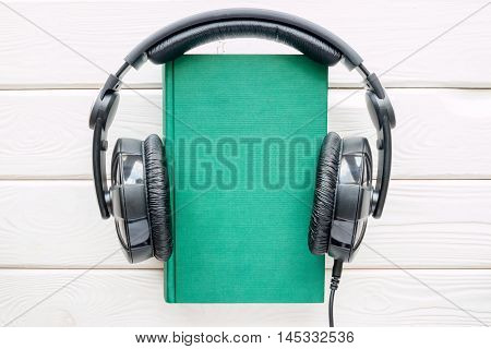 Headphones on the book in hardcover on white background