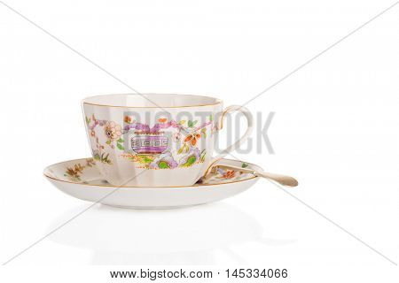 Antique fluted teacup and saucer with spoon on a white background