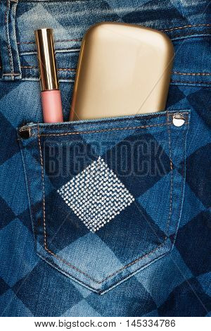 Cosmetics sticks out of the pocket of his jeans with rhinestones as background