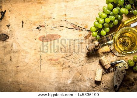 Bunch of white grapes with wine, a corkscrew and stoppers. On wooden background.