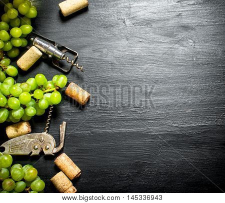 Wine corks with corkscrew and grape branch. On a black wooden background.