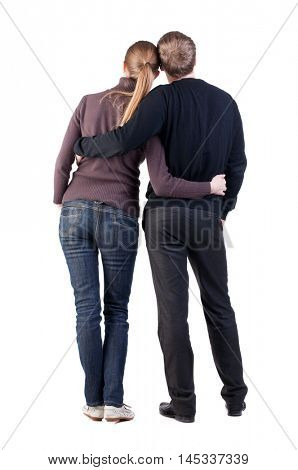 Back view of young couple (man and woman) hug and look into the distance. beautiful friendly girl and guy together. Rear view. Isolated over white background. heterosexual couple hugging and leaning