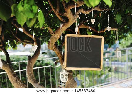 Blackboard lantern and heart shaped decorations on a tree for the wedding party