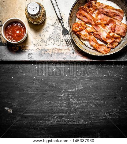 Fried bacon in a frying pan with the sauce. On a black wooden background.