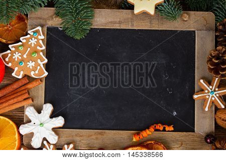 christmas gingerbread cookies with fir tree twigs frame with blackboard