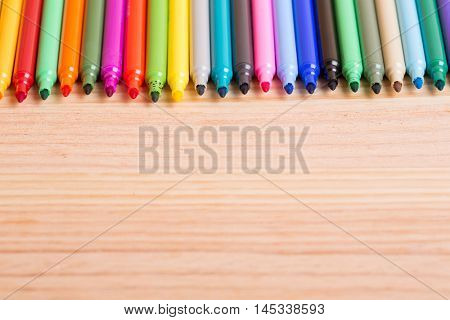 Colorful markers pens on a wooden table