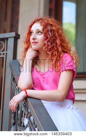 Happy smiling beautiful young woman with curly red hair with colorful hair pieces wearing bouffant skirt and magenta blouse standing on staircase