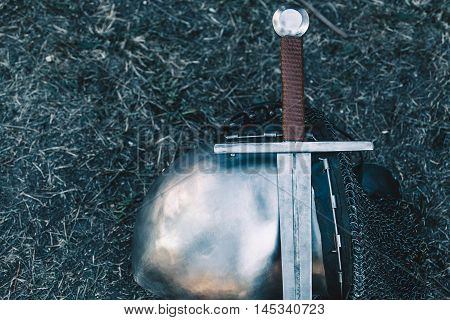 Knight's helmet and shiny metal lying on the ground it put an old steel sword with leather handle.