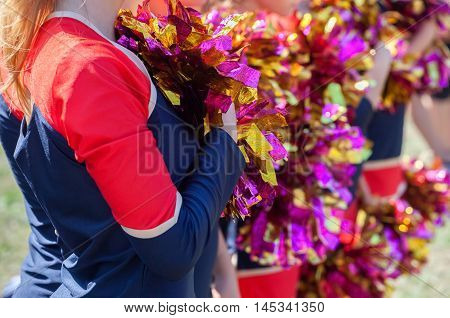 Cheerleaders holding multicolored pom-poms in their hands.