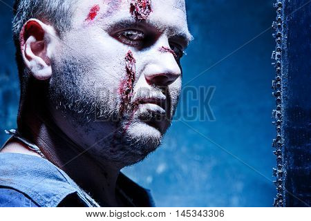 Bloody Halloween theme: crazy killer as young man with blood on dark
