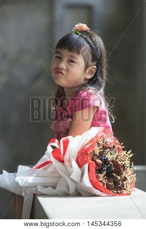 smiling face of asian kid happiness emotion and dry flowers bouquet beside