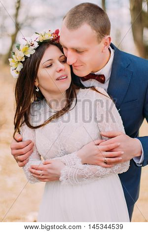 Wedding portrait of stylish newlywed bride and groom happily embracing outdoor with leafless trees at background.